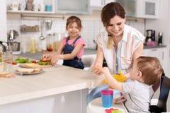 Gospodyni domowej narządzania gość restauracji z jej dziećmi zdjęcia royalty free
