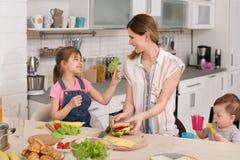 Gospodyni domowej narządzania gość restauracji z jej dziećmi na kuchni obraz royalty free