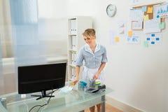 Gosposi cleaning biurko z piórkowym duster zdjęcia stock