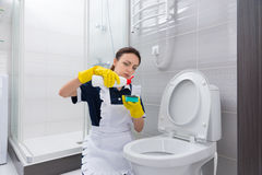 Gosposi kładzenia cleaner na gąbce nad toaleta Obraz Stock