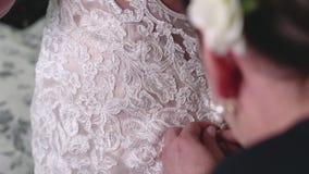 Gosposia honor i matka panna młoda pomagamy panna młoda zamkniętym guzikom na koronkowej ślubnej todze zdjęcie wideo