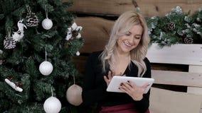Gosposia komunikuje na internecie na jej pastylce w Bożenarodzeniowej atmosferze zdjęcie wideo
