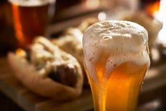 Goss frisch bernsteinfarbiges Bier im Becher, der mit Bratwürsten gedient wurde lizenzfreies stockbild
