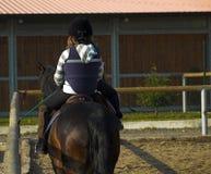 Gosse à l'école d'équitation Photographie stock libre de droits