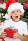 Gosse étonné heureux avec le cadeau de Noël Image stock