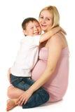 Gosse étreignant sa mère enceinte Image libre de droits