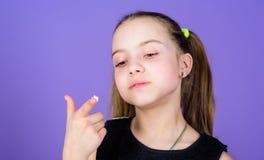 Gosse affam? Le visage de sourire de fille tient le fond violet doux de guimauves ? disposition Concept de pied de mouton Fille d image stock