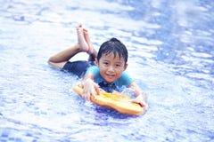 Gosse asiatique joyeux à la piscine Photos stock