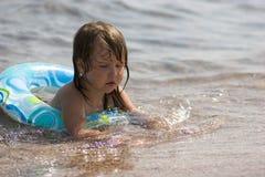 Gosse dans la bouée jouant avec le sable Photographie stock libre de droits