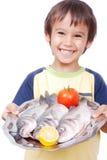 Gosse de sourire avec trois poissons frais sur la table Image libre de droits