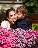 Gosse embrassant la mère extérieure Photo stock