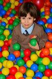 Gosse heureux dans la cour de jeu avec les billes colorées image stock