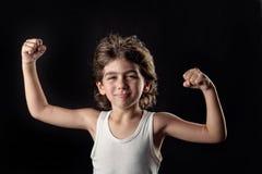 Gosse intense affichant ses muscles photo stock