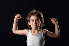 Gosse intense affichant ses muscles images libres de droits