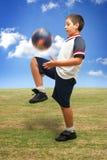 Gosse jouant au football à l'extérieur Images libres de droits
