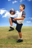 Gosse jouant au football à l'extérieur Photo stock