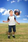 Gosse jouant au football à l'extérieur Images stock