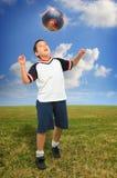 Gosse jouant au football à l'extérieur Photo libre de droits