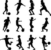 Gosse jouant au football Photographie stock