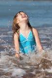 Gosse jouant dans l'océan Images stock