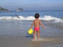 Gosse jouant dans la plage photo stock