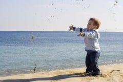 Gosse jouant sur la plage Photographie stock