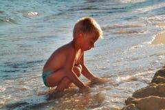 Gosse jouant sur la plage Photos stock
