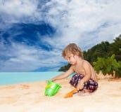 Gosse jouant sur le bord de la mer Photo stock