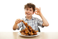 Gosse mangeant le pilon de poulet Image libre de droits