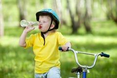 Gosse mignon d'enfant sur la bicyclette et l'eau potable Image stock
