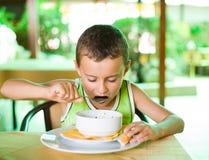 Gosse mignon mangeant du potage Photo libre de droits
