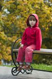 Gosse s'asseyant sur le banc à l'extérieur Photo libre de droits