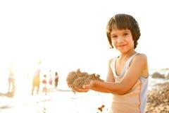 Gosse sur la plage dans le jeu de sable, Photos libres de droits