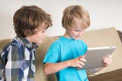 Gosse travaillant sur un ordinateur de tablette Image libre de droits