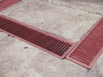 Gossen-stürmen rote Gitter-Entwässerungsstraßenabwasserkanäle Abfluss Lizenzfreies Stockbild