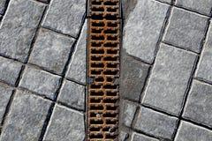 Gossenentwässerung, umfasst mit Stahlgitter Lizenzfreies Stockfoto