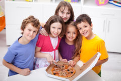 Gosses à la maison avec la pizza Photographie stock