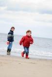 Gosses à la plage de l'hiver Photos stock