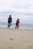 Gosses à la plage de l'hiver Images stock