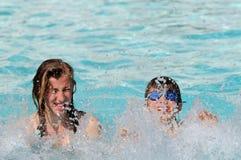 Gosses éclaboussant dans la piscine Photographie stock libre de droits