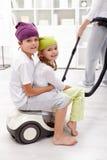 Gosses aidant leur mère nettoyant la salle Photo libre de droits