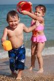 Gosses arrosant sur la plage 2 Image libre de droits