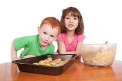 Gosses avec des cookes de puce de chocolat à faire cuire au four Photos libres de droits