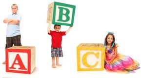 Gosses avec l'ABC dans des blocs d'alphabet Photo stock