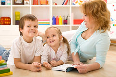 Gosses ayant des histoires du relevé d'amusement avec leur maman images stock