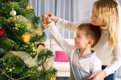 Gosses décorant un arbre de Noël Photographie stock libre de droits