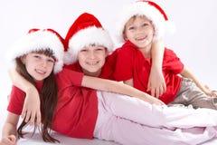 Gosses dans des chapeaux de fête de Santa Photos libres de droits