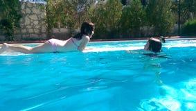 Gosses dans la piscine Photos libres de droits
