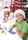 Gosses effectuant des cartes de voeux de Noël Photographie stock libre de droits