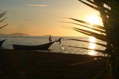 Gosses et bateau dans le coucher du soleil Photographie stock libre de droits